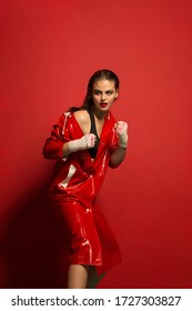 Woman in red latex coat on red background in combat pose with bandages on her hands . Woman fight in red on red background .