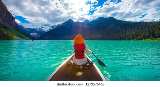 A woman in red life jacket canoeing in Lake Louise with torquoise lake and bluesky , Lake Louise, Alberta, Canada