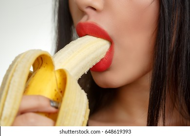 Woman with Red Lips Eating Banana. Blowjob Concept