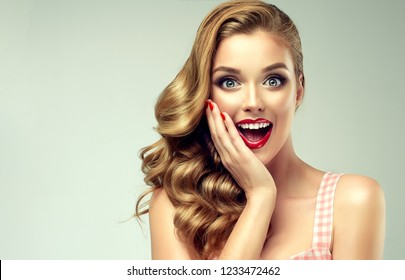 Woman with red lips and nails surprise holds cheeks by hand .Beautiful girl  with curly hair surprised and shocked looking on you . Presenting your product. Expressive facial expressions