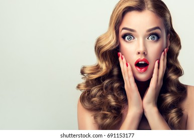 Woman with red lips and nails surprise holds cheeks by hand .Beautiful girl  with curly hair surprised and shocked looks on you . Presenting your product. Expressive facial expressions