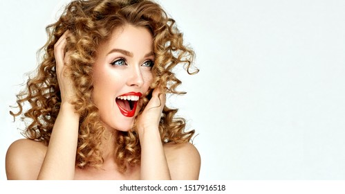 Woman with red lips  shouts in surprise  joy.Beautiful girl   curly hair surprised and shocked looks on you and  screaming with delight .Presenting your product. Expressive facial expressions emotions