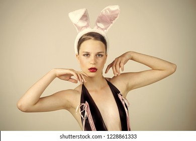 Woman with red lips wearing rabbit ears. Easter holiday concept. Playboy girl posing on grey background. Sexy bunny model.