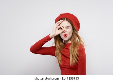 A woman in red looks through her fingers.