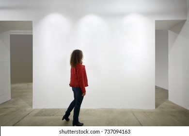 Woman in red looks at white wall in exhibition of art, back view