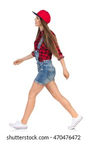 Woman in red lumberjack shirt, jeans shorts and white sneakers walking and looking away. Side view. Full length studio shot isolated on white.