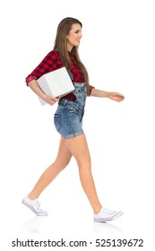 Woman in red lumberjack shirt, jeans dungarees shorts and white sneakers walking, holding white box under the arm and looking away. Side view. Full length studio shot isolated on white.