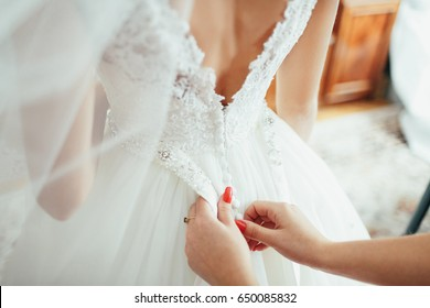 Woman with red nails fixes dress on bride's back