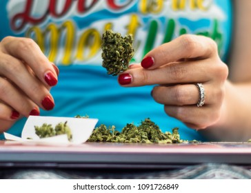 Woman with red nails holding up a trimmed marijuana bud that is being used for rolling a joint.