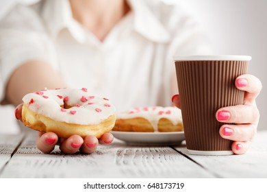 Woman with red nails sitting and holding a donut and hot cup of coffee