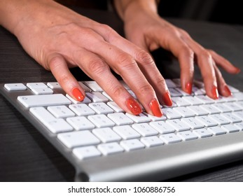 Woman with red nails typing on wireless keyboard