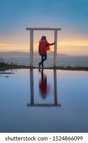 Woman with a red raincoat contemplating the ocean from a frame of a door