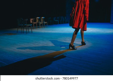 A woman in a red raincoat is walking across the stage of the theater