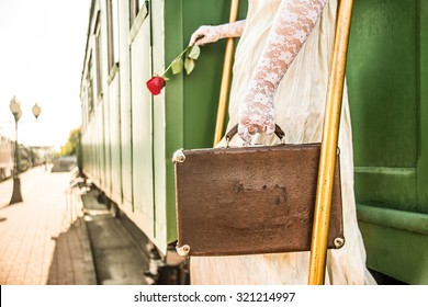 Woman with red rose  sit on stair of wagon. Railway station against retro vintage old locomotive in perspective. Young adult girl hold in hands one flower and read book Female wear gloves and dress