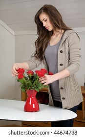 Woman with red roses in a red vase