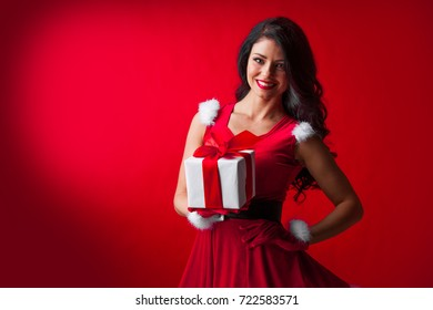 Woman in red Santa Claus outfit holding christmas gift box