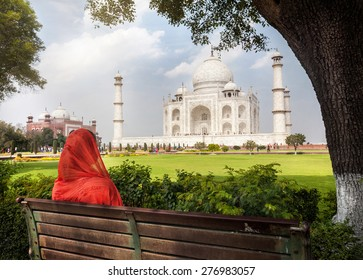 Woman in red scarf sitting on the bench in the shadow and looking at Taj Mahal in Agra, Uttar Pradesh, India