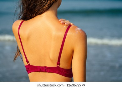 woman in a red sexy bathing suit applying protective lotion before sunbathing at beach on the background of the sea and colorful walls.fitness bikini model girl and a spray bottle of SPF
