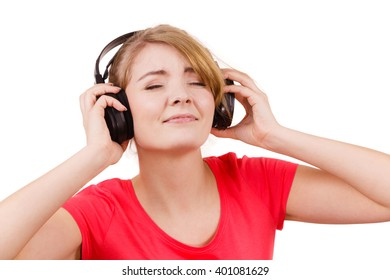 Woman in red shirt big headphones listening music mp3. Smiling female model on white. People leisure happiness concept.