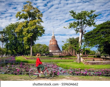 Woman in red shirt riding bicycle looking at old Buddhist temple in Sukhothai historical park, Thailand