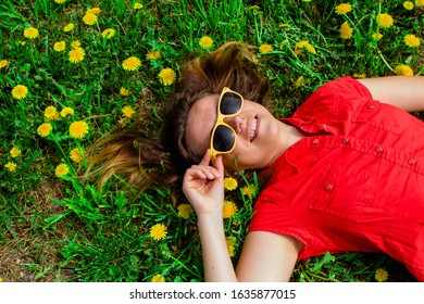 Woman in red shirt and yellow sunglasses lying on the field of dandelions. Top view