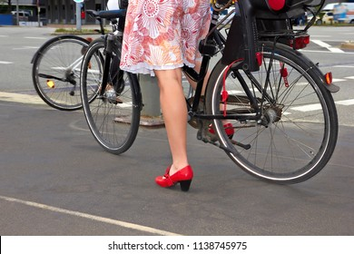 Woman in red shoes on bicycle