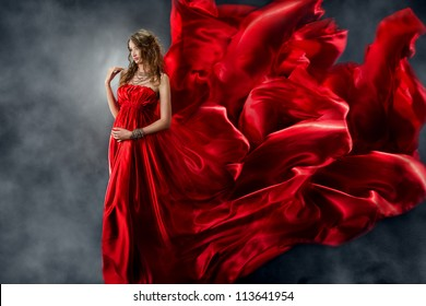 Woman in red silk dress waving on wind. Flying and fluttering gown cloth over gray background