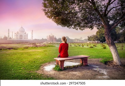 Woman in red sitting on the bench in Mehtab Bagh and looking at Taj Mahal in Agra, Uttar Pradesh, India