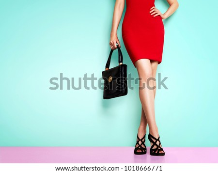 02e4a85d3833 Woman with red skirt standing with black purse bag and shoes. Isolated on  light blue
