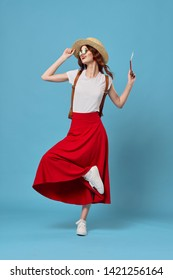 A woman in a red skirt and white t-shirt on a blue background lifted her leg upward traveling airplane tickets