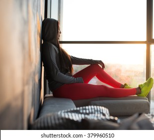 A woman in a red sport pants and in a yellow choes sitting near window and looking outside.