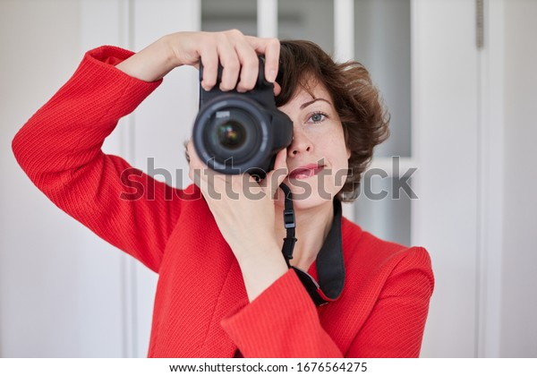 Woman in red spring casual clothes, with photo camera isolated on white background. Female passenger traveling abroad to travel on weekends getaway. Business photographer concept