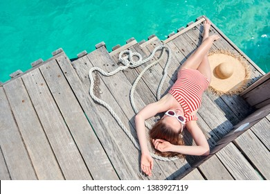 Woman in red striped one-piece swimsuit lying on wooden jetty. Summer vacation at Maldives.
