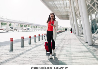 Woman with red suitcase walks along the airport and talks on the phone