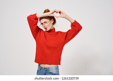 A woman in a red sweater holds hands in the form of a heart