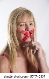 Woman with red tape stretched across her mouth in a concept of keeping quiet