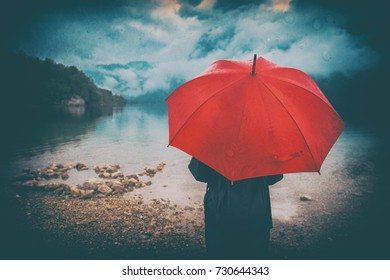 Woman with red umbrella contemplates on rain in front of a lake. Sad and lonely female person looking into distance. Grunge editing with dirt, noise, splotches and dust.