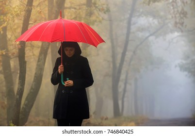 Woman with red umbrella and foggy forest