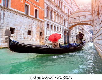 Woman with a red umbrella in Gondola passing over Bridge of Sighs in Venice, Italy