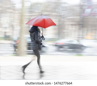 Woman with red umbrella on busy street on rainy day