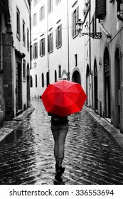 Woman with red umbrella on cobblestone street in the old town. Wind, rain, stormy weather. Color in black and white conceptual, idea. Vintage, retro style.