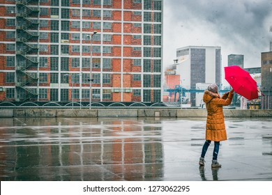 Woman with red umbrella is walking in city during blizzard. Snowing in industrial city.