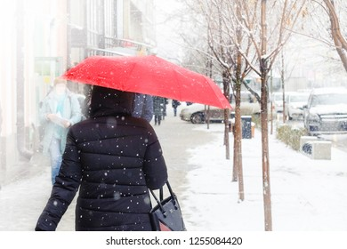 A woman with a red umbrella is walking on a snow-covered sidewalk during a snowstorm, snowfall, sleet.