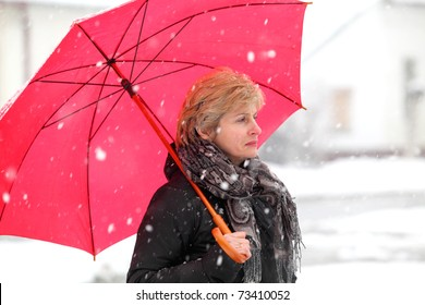 Woman with red umbrella in a winter day while snowing