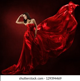 Woman in red waving dress dancing with flying fluttering fabric
