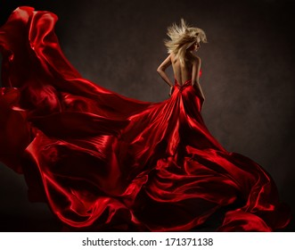 Woman in red waving dress with flying gown fabric. Back side view