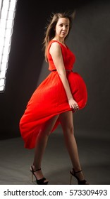 Woman in red waving dress with flying fabric. Young beauty woman in fluttering red dress. Fashion photo of young magnificent woman in red dress. Studio photo