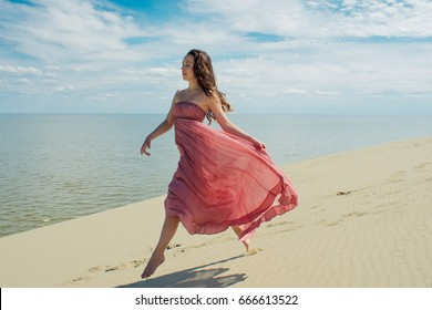 Woman in red waving dress with flying fabric runs on background of dunes. Skyline and the sea