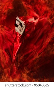 Woman in red waving silk dress as fire flame. Artistic Beauty Model girl posing in flying long gown