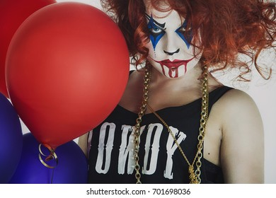 Woman, red-haired clown with a balloon, Halloween. Scary face